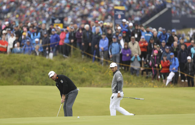 Northern Ireland's Graeme McDowell, left putts on the 14th green watched by Xander Schauffele of the United States during the first round of the British Open Golf Championships at Royal Portrush in Northern Ireland, Thursday, July 18, 2019.(AP Photo/Peter Morrison)
