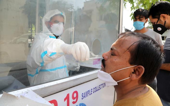 An Indian medical official collects a swab sample for a coronavirus and COVID-19 disease test at government medical college hospital in Jammu, India, 29 September 2020. - JAIPAL SINGH/EPA-EFE/Shutterstock