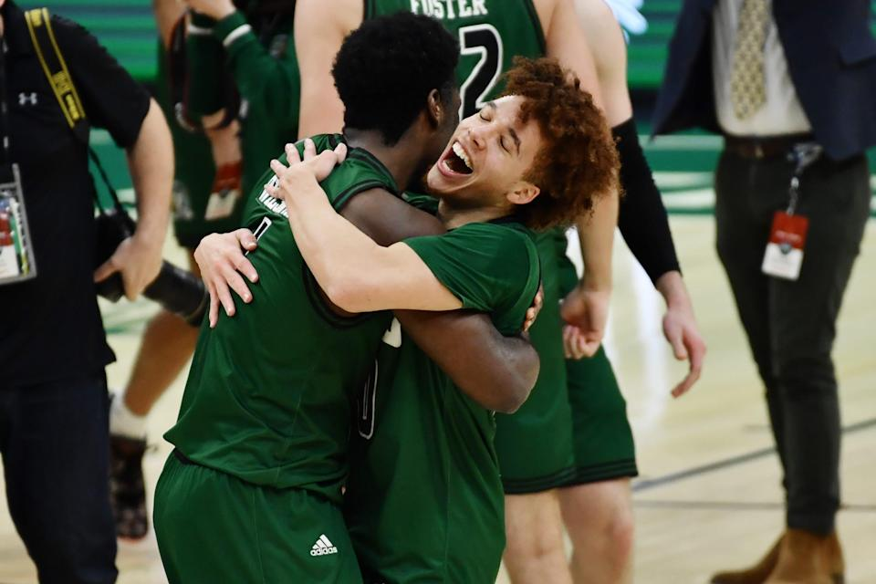 Ohio guard Jason Preston, right, hugs forward Dwight Wilson III in celebration after the Bobcats beat the Buffalo Bulls to win the MAC championship at Rocket Mortgage FieldHouse in Cleveland, March 13, 2021.