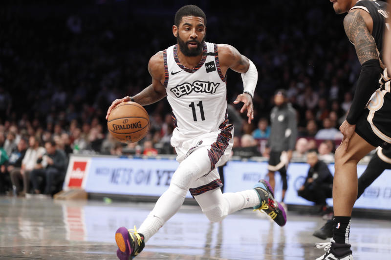 Brooklyn Nets guard Kyrie Irving (11) drives around Atlanta Hawks defense during the second half of an NBA basketball game, Sunday, Jan. 12, 2020, in New York. The Nets defeated the Hawks 108-86. (AP Photo/Kathy Willens)