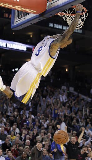 Golden State Warriors' Monta Ellis hangs off the rim after scoring against the Memphis Grizzlies during the first half of an NBA basketball game Wednesday, March 7, 2012, in Oakland, Calif. (AP Photo/Ben Margot)