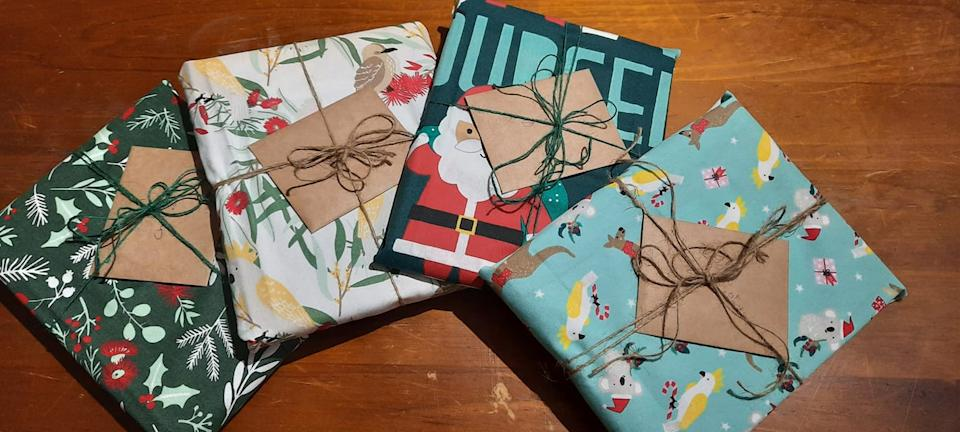 Four Christmas gifts wrapped in Kmart Christmas-themed tea towels instead of traditional wrapping paper