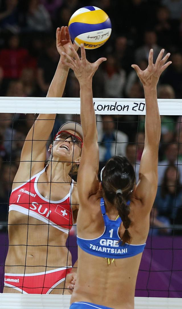 Maria Tsiartsiani, right, from Greece tries to block Simone Kuhn, left, from Switzerland during their Beach Volleyball match at the 2012 Summer Olympics, Saturday, July 28, 2012, in London. (AP Photo/Petr David Josek)