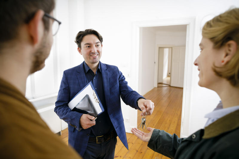 BERLIN, GERMANY - OCTOBER 25: Posed scene on the topic of property market. A estate agent hands flat keys to a young couple on October 25, 2018 in Berlin, Germany. (Photo Illustration by Thomas Trutschel/Photothek via Getty Images)