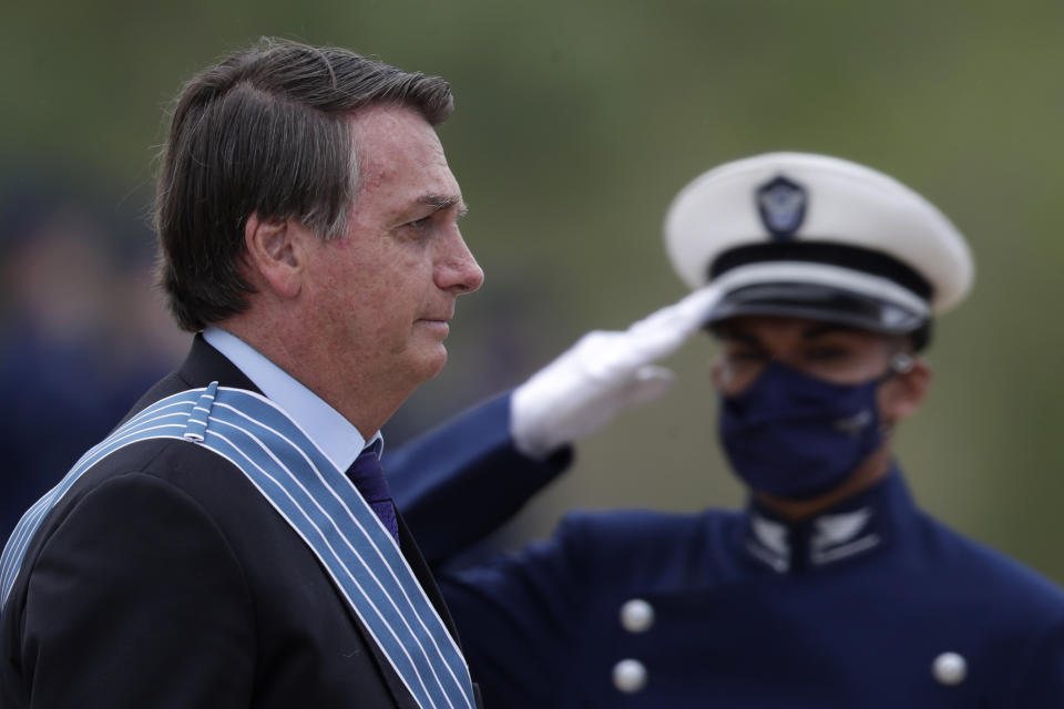 Brazil's President Jair Bolsonaro receives military honors as he arrives for a ceremony in honor of Aviator Day at the air base in Brasilia, Brazil, Friday, Oct. 23, 2020. (AP Photo/Eraldo Peres)