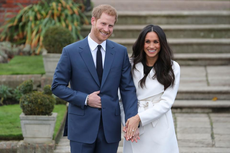 Britain's Prince Harry and his fiancée US actress Meghan Markle pose for a photograph in the Sunken Garden at Kensington Palace in west London on November 27, 2017, following the announcement of their engagement. Britain's Prince Harry will marry his US actress girlfriend Meghan Markle early next year after the couple became engaged earlier this month, Clarence House announced on Monday. / AFP PHOTO / Daniel LEAL-OLIVAS        (Photo credit should read DANIEL LEAL-OLIVAS/AFP via Getty Images)
