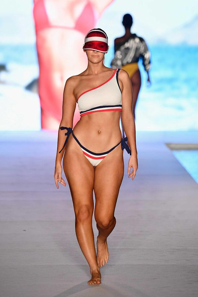 <p>A model walks the runway wearing a patriotic-style sporty bikini set and visor for the 2018 <em>Sports Illustrated</em> swimsuit show during Miami Swim Week at the W South Beach hotel on July 15. (Photo: Alexander Tamargo/Getty Images for Sports Illustrated) </p>