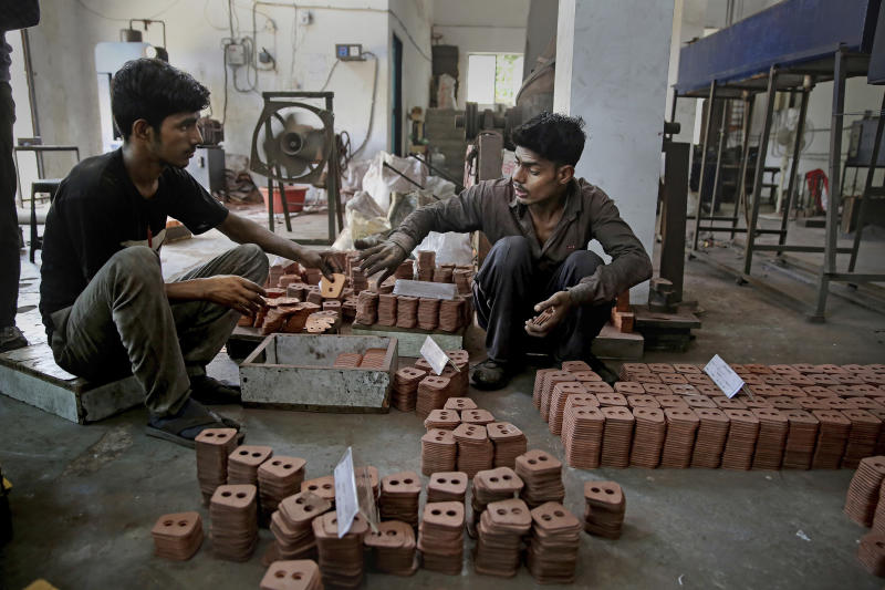 FILE - In this Sept. 5, 2019, file photo, Indian workers prepare packing of clutch buttons at an auto component manufacturing factory on the outskirts of New Delhi, India. Asian shares advanced Friday, Sept. 20, 2019, and India's benchmark jumped 5.4% after the government announced plans to cut corporate taxes. (AP Photo/Altaf Qadri, File)