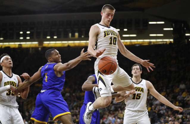 Iowa guard Joe Wieskamp (10) fights for a rebound with UKMC forward Jordan Giles (5) during the first half of an NCAA college basketball game, Thursday, Nov. 8, 2018, in Iowa City, Iowa. (AP Photo/Charlie Neibergall)