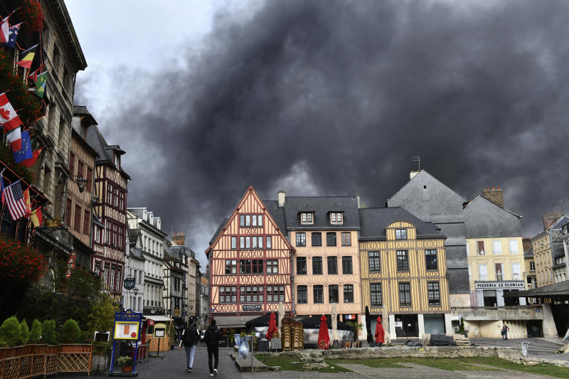 Black smoke is pictured from the historical center of Rouen, Normandy, after a fire broke at a chemical plant Thursday, Sept.26, 2019. An immense mass of black smoke is rising over Normandy as firefighters battle a blaze at a chemical plant, and authorities closed schools in 11 surrounding towns and asked residents to stay indoors. (AP Photo/Stephanie Peron)