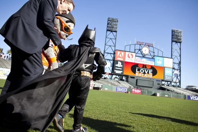 SAN FRANCISCO, CA - NOVEMBER 15: Larry Baer, CEO of the San Francisco Giants, and the team's mascot Lou Seal escort leukemia survivor Miles, 5, dressed as BatKid, to the outfield to see a message on the scoreboard as part of a Make-A-Wish foundation fulfillment at AT&T Park November 15, 2013 in San Francisco. The Make-A-Wish Greater Bay Area foundation turned the city into Gotham City for Miles by creating a day-long event bringing his wish to be BatKid to life. (Photo by Ramin Talaie/Getty Images)