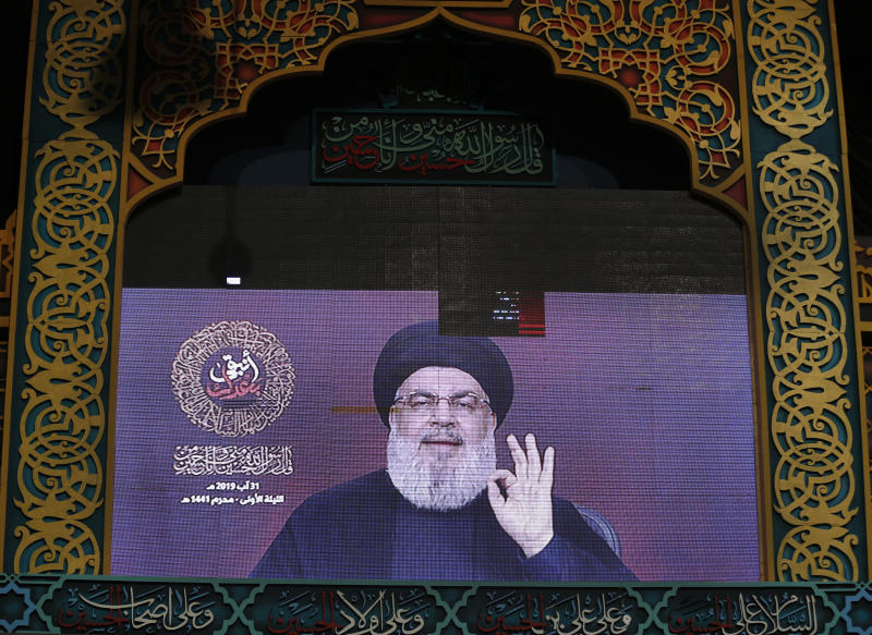 """Hezbollah leader Sayyed Hassan Nasrallah, speaks via a video link, during the first day of Ashoura, in the southern suburb of Beirut, Lebanon, Saturday, Aug. 31, 2019. The leader of Lebanon's Hezbollah categorically denied Israeli claims about his group having factories to produce precision-guided missiles in Lebanon, saying such """"likes"""" were an attempt to justify Israeli attacks against the country. (AP Photo/Hussein Malla)"""