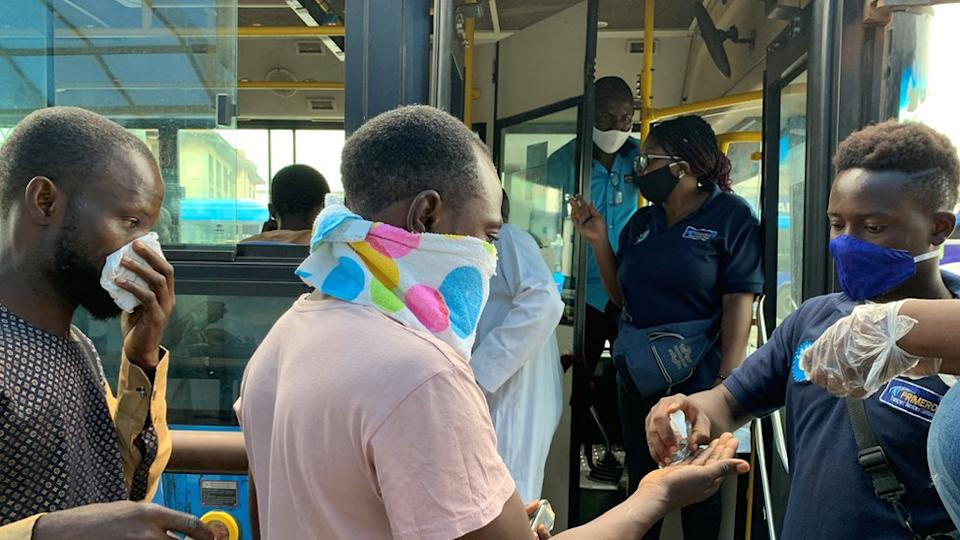 Passengers boarding a bus in Lagos being given hand sanitiser