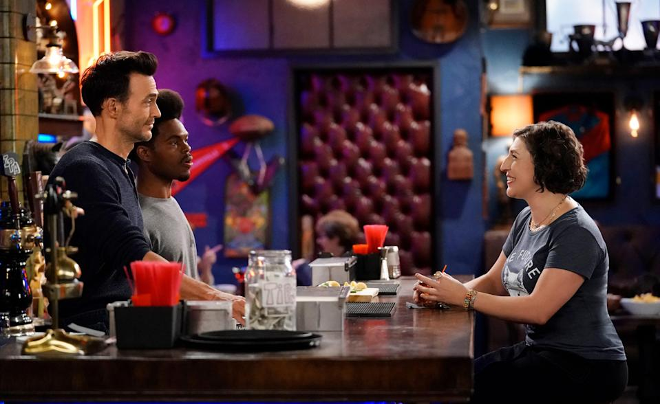 Kat (Mayim Bialik), right, receives a pleasant surprise when friend and college crush Max (Cheyenne Jackson), left, returns to town to work at a bar run by Carter (Julian Gant) in the new Fox comedy, 'Call Me Kat.'