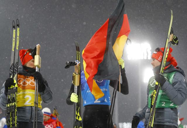 Nordic Combined Events - Pyeongchang 2018 Winter Olympics - Men's Team 4 x 5 km Final - Alpensia Cross-Country Skiing Centre - Pyeongchang, South Korea - February 22, 2018 - The wind blows the German flag as Johannes Rydzek of Germany celebrates with teammates Eric Frenzel and Fabian Riessle. REUTERS/Kai Pfaffenbach