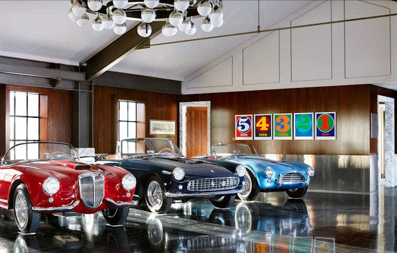 A 1955 Lancia Aurelia B24S Spider America, A 1960 Ferrari 250 GT Cabriolet Series II, and a 1964 Shelby Cobra 289 lined up in the main room. On back wall, a set of Robert Indiana numbers.