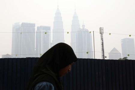 A woman passes by Petronas Twin Towers shrouded in haze in Kuala Lumpur