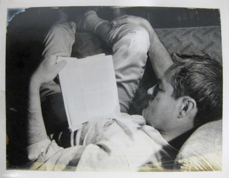 In this circa 1961 file photo provided by the New York Public Library, a curled-up Timothy Leary reads a book. Leary saved thousands of documents, correspondence and writings relating to his scientific research into psychedelic drugs in the 1960s, much of it never published but now available to scholars and the public at the New York Public Library, which purchased the collection in 2011 from the Leary estate. (AP Photo/File, New York Public Library, Manuscripts and Archives Division)