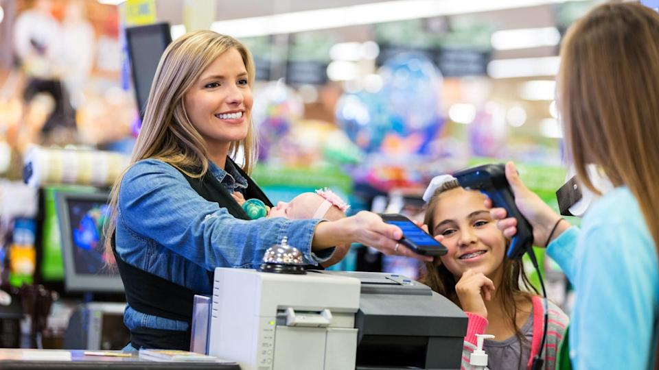 Mid adult Caucasian woman is smiling while using her smart phone to pay for purchases or use coupons in local grocery store.