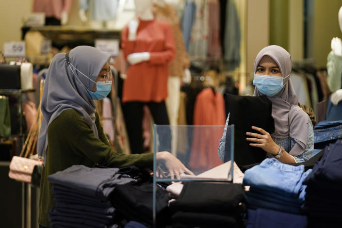 Shoppers wearing a face mask to help curb the spread of the coronavirus shopping at mall in Putrajaya, Malaysia, Monday, Oct. 5, 2020. Prime Minister Muhyiddin Yassin says he will self-quarantine after a Cabinet minister he was in contact with tested positive for the coronavirus. (AP Photo/Vincent Thian)