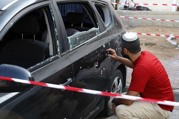 <p>An Israeli man checks damages on his car after a rocket fired by militants from the Gaza Strip fell naerby in the southern Israeli town of Sderot on Aug. 9, 2018.(Photo: Jack Guez/AFP/Getty Images) </p>