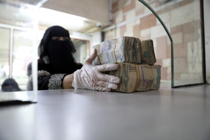 Employee takes bundles of Yemeni Riyal at the Central Bank of Yemen in Sanaa