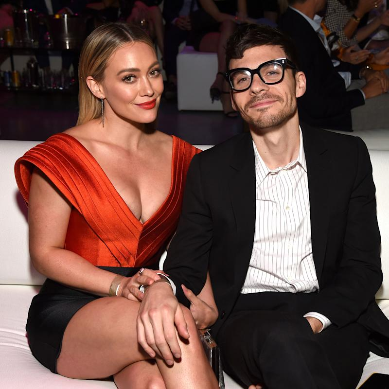 Hilary Duff (left) and Matthew Koma (right) sit with Duff holding Koma's arm on her leg