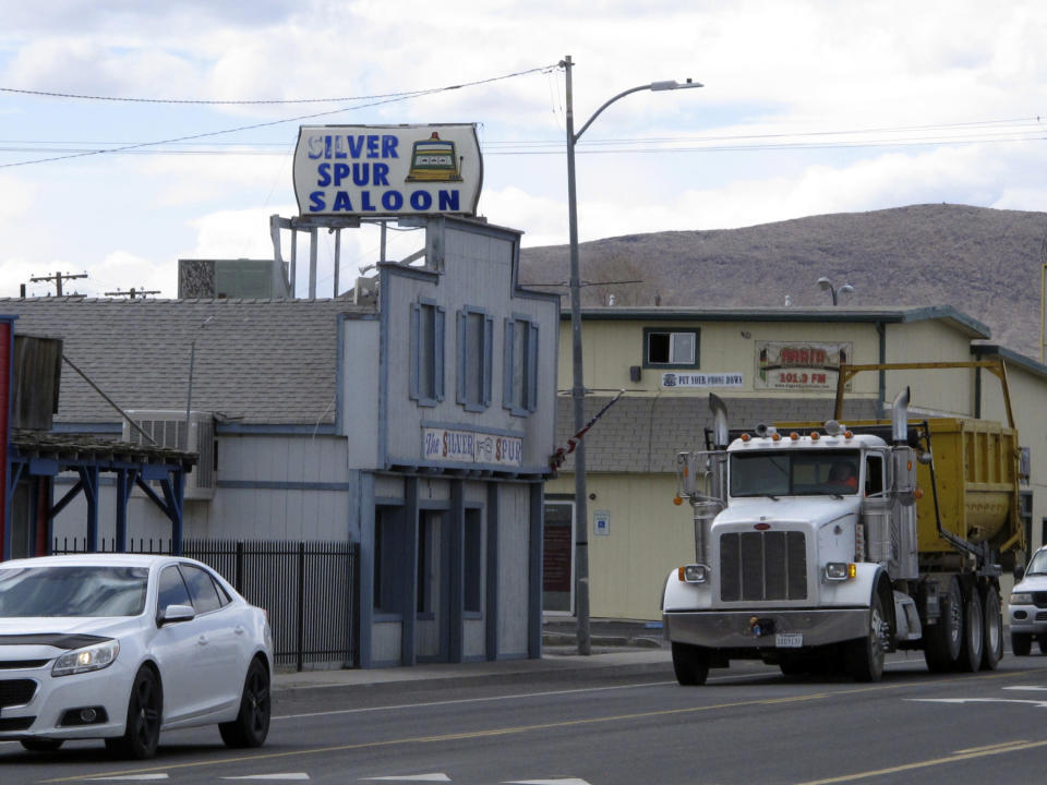 Traffic passes in front of the Silver Spur Saloon on Main Street in Fernley, Nev. about 30 miles east of Reno Thursday, March 18, 2021, The town founded a century ago by pioneers lured to the West with the promise of free land and cheap water is suing the U.S. government over plans to renovate an earthen irrigation canal that burst and flooded nearly 600 homes in Fernley in 2008. (AP Photo/Scott Sonner).