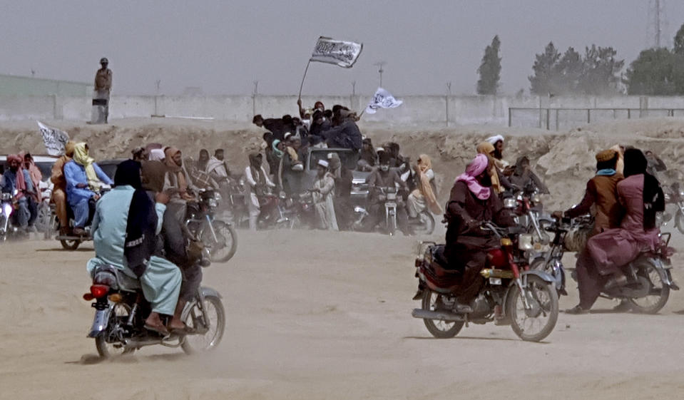 Supporters of the Taliban carry the Taliban's signature white flags in the Afghan-Pakistan border town of Chaman, Pakistan, Wednesday, July 14, 2021. The Taliban are pressing on with their surge in Afghanistan, saying Wednesday that they seized Spin Boldaka, a strategic border crossing with Pakistan — the latest in a series of key border post to come under their control in recent weeks. (AP Photo/Tariq Achkzai)