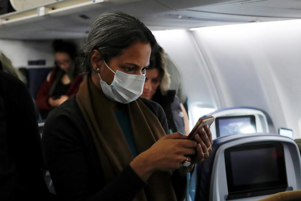 A woman in a face mask checks her phone after landing on a flight from San Francisco to New York City, after further cases of coronavirus were confirmed in New York, at JFK International Airport in New York, U.S., March 5, 2020. REUTERS/Shannon Stapleton
