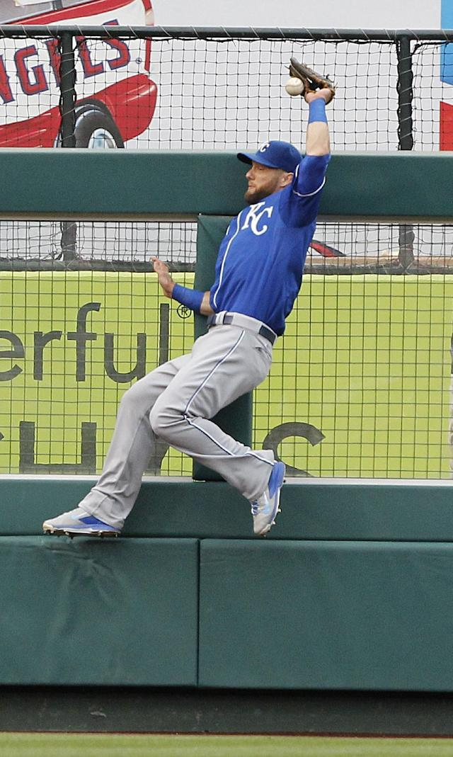 Kansas City Royals left fielder Alex Gordon leaps at the fence and reaches back to put his glove on the ball hit by Los Angeles Angels' Albert Pujols in the fifth inning of a baseball game Saturday, May 24, 2014, in Anaheim, Calif. After video review, it was ruled a double, and is the 2,400th hit of Pujols' career. (AP Photo/Alex Gallardo)
