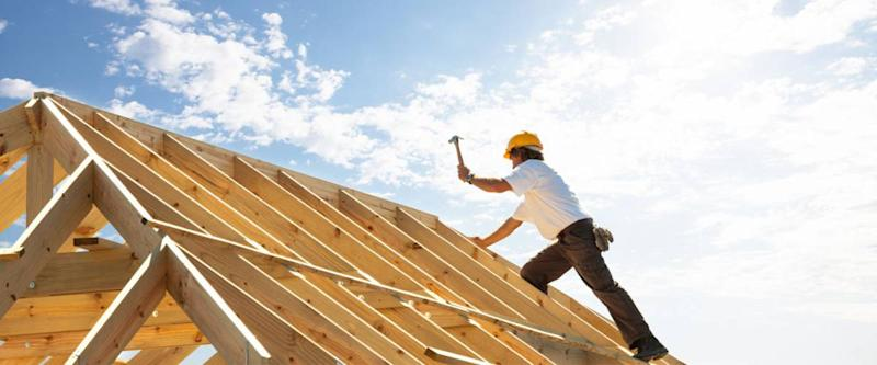 A roofer gets to work building a house.