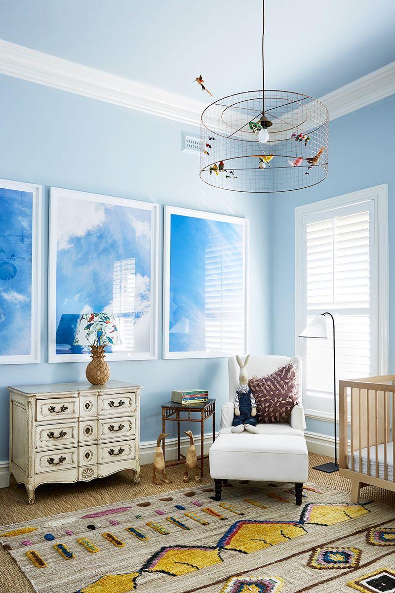 """<p>In this baby's room designed by <a href=""""https://tamsinjohnson.com/"""" rel=""""nofollow noopener"""" target=""""_blank"""" data-ylk=""""slk:Tamsin Johnson"""" class=""""link rapid-noclick-resp"""">Tamsin Johnson</a>, the timeless pieces—like the ottoman and chair set, framed photographs, and traditional dresser—give the room a refined edge that will age well. To balance it out, she chose a whimsical pendant light. Plus, it draws your eye up (where the baby will be looking from their crib) and is an unexpected twist on the space. </p>"""