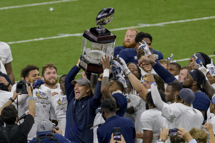 Georgia Southern coach Chad Lunsford and players hold the trophy after a victory over Louisiana Tech in the New Orleans Bowl NCAA college football game in New Orleans, Wednesday, Dec. 23, 2020. (AP Photo/Matthew Hinton)