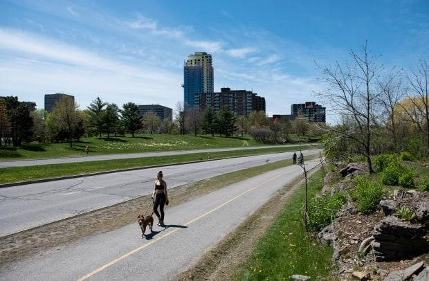 People walk along a path beside the Sir John A. Macdonald Parkway in Ottawa in May 2020. Three Ottawa city councillors are calling for the road to be renamed in light of the discovery of the remains of 215 children at a former residential school in B.C., and the role the first prime minister's government played in that legacy. (Justin Tang/Canadian Press - image credit)