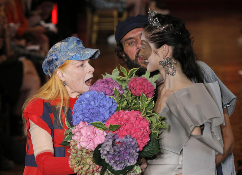 British fashion designer Vivienne Westwood, left, gets flowers from a model after the presentation of her ready to wear Spring-Summer 2013 collection, in Paris, Saturday, Sept.29, 2012. (AP Photo/Francois Mori)