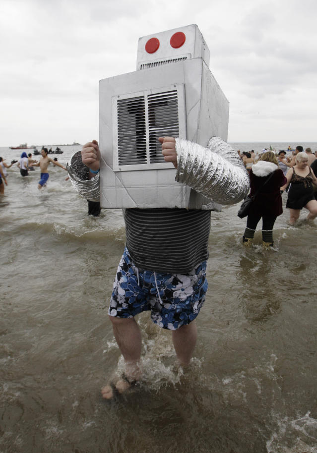 Picking up on a theme related to Superstorm Sandy, which hit Coney Island hard, a man dressed as a boiler tests the water during the 110th annual Coney Island Polar Bear Club ocean swim at Coney Island in New York, Tuesday, Jan. 1, 2013. (AP Photo/Kathy Willens)