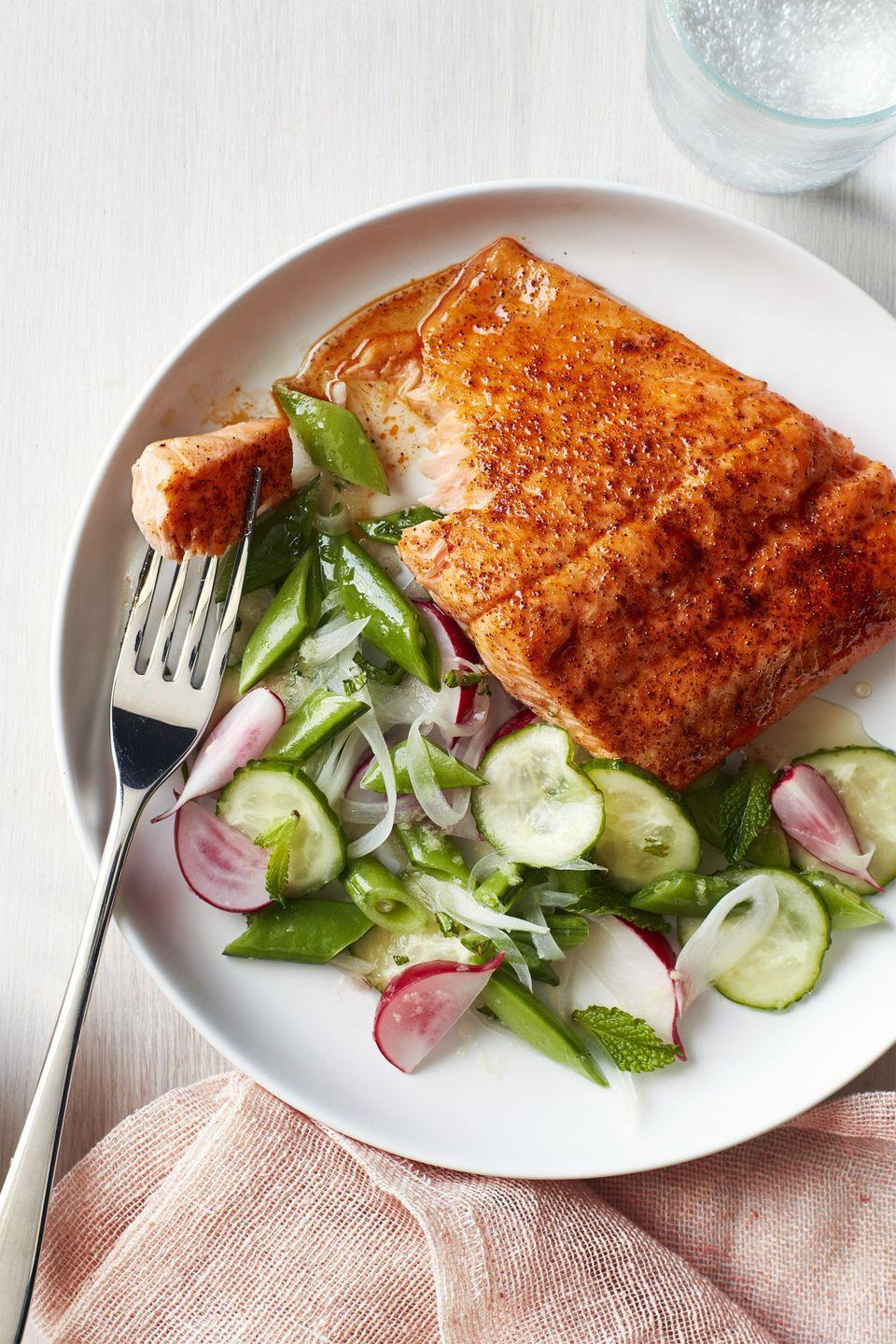 """<p>A light radish and snap pea salad balances out the smoky salmon. And it only takes 20 minutes!</p><p><em><a href=""""https://www.womansday.com/food-recipes/food-drinks/recipes/a58512/roasted-blackened-salmon-snap-pea-salad-recipe/"""" rel=""""nofollow noopener"""" target=""""_blank"""" data-ylk=""""slk:Get the Roasted Blackened Salmon with Snap Pea Salad recipe."""" class=""""link rapid-noclick-resp"""">Get the Roasted Blackened Salmon with Snap Pea Salad recipe.</a></em></p>"""