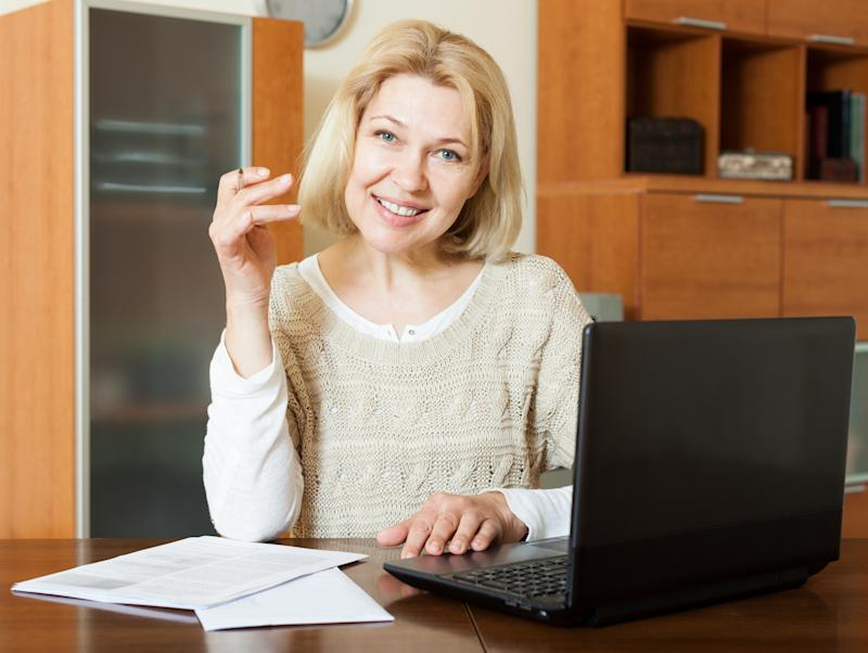 A mature woman checking her earnings history on a laptop.