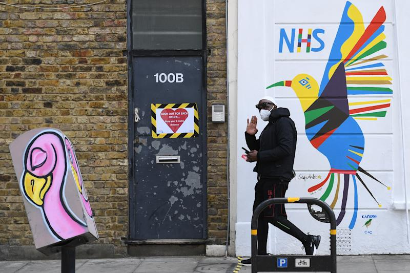 A person walks past a mural painted on the side of Safedale pharmacy in Stoke Newington Church St, London in support of the NHS, as the UK continues in lockdown to help curb the spread of the coronavirus. (Photo by Stefan Rousseau/PA Images via Getty Images)