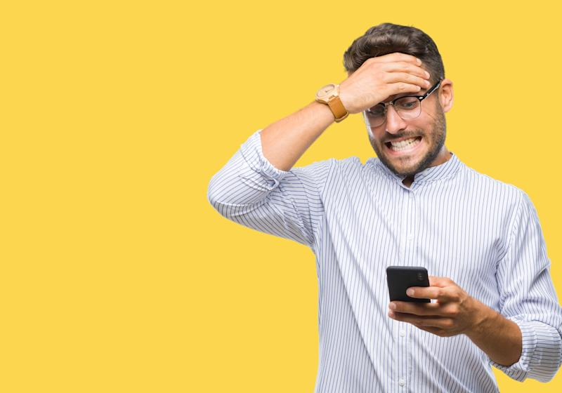 Young handsome man texting using smartphone over isolated background stressed with hand on head, shocked with shame and surprise face, angry and frustrated. Fear and upset for mistake. (Young handsome man texting using smartphone over isolated backgro