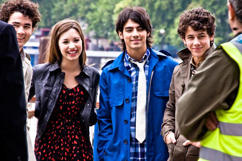 An older photo of the Jonas brothers smiling with Demi Lovato