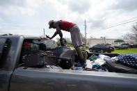 Bernie Murray rearranges luggage in Lake Charles, La., as he returns with eight family members in one truck, after evacuating from Hurricane Laura, Sunday, Aug. 30, 2020. (AP Photo/Gerald Herbert)