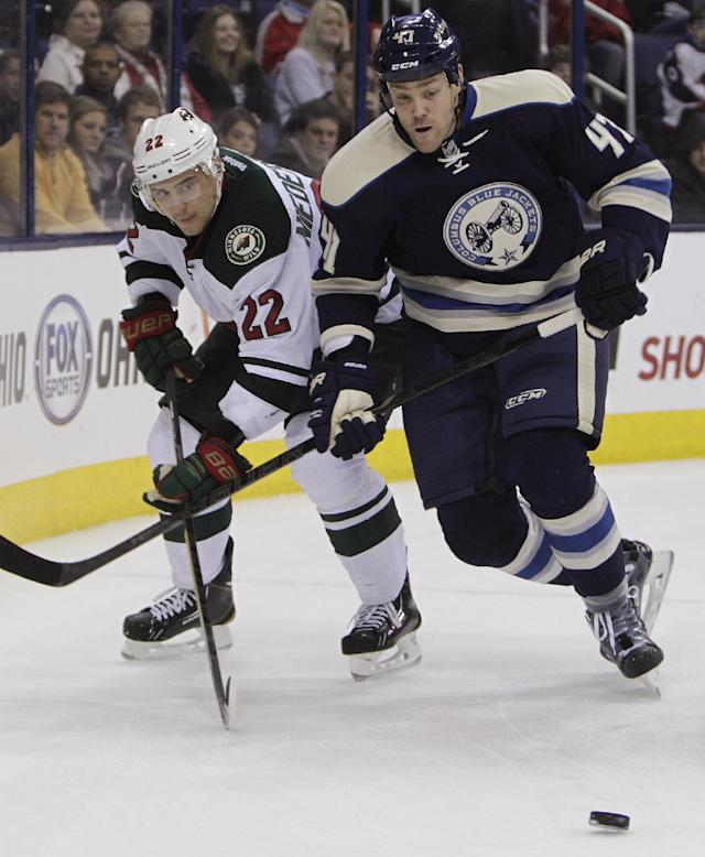 Minnesota Wild's Nino Niederreiter, left, of Switzerland, and Columbus Blue Jackets' Dalton Prout chase a loose puck during the third period of an NHL hockey game on Friday, Dec. 6, 2013, in Columbus, Ohio. The Blue Jackets won 4-0. (AP Photo/Jay LaPrete)