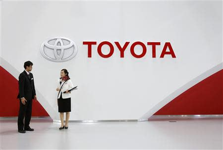 Staff stand under Toyota Motor's logo at the company's showroom in Tokyo