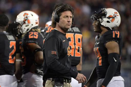 FILE - In this Dec. 28, 2017, file photo, Oklahoma State head coach Mike Gundy, center, walks back to the sideline after a huddle on the field during the first half of the Camping World Bowl NCAA college football game against Virginia Tech, in Orlando, Fla. For the first time in more than three years, Oklahoma State coach Mike Gundy will have a new starting quarterback. Mason Rudolph started 41 games for the Cowboys and left with many of the most significant school records. Taylor Cornelius appears ready to step in. The 6-foot-6, 232-pound senior has taken control of the position during the spring.(AP Photo/Phelan M. Ebenhack, File)