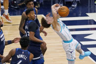 Charlotte Hornets' LaMelo Ball, right, loses the ball after being fouled by Minnesota Timberwolves' Jaylen Nowell (4) in the second half of an NBA basketball game Wednesday, March 3, 2021, in Minneapolis. (AP Photo/Jim Mone)