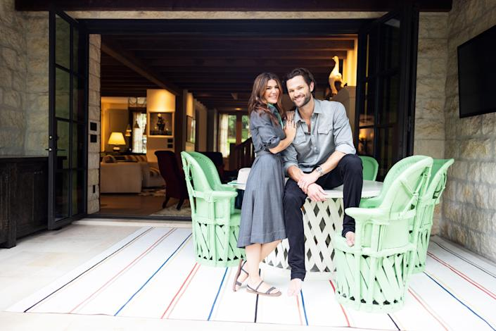 Jared and Genevieve pictured in one of the outdoor areas of the home. The minty green painted table and chairs are placed atop a Perennials outdoor rug.