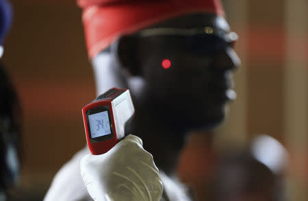 Man has his temperature taken using an infrared digital laser thermometer at the Nnamdi Azikiwe International Airport in Abuja