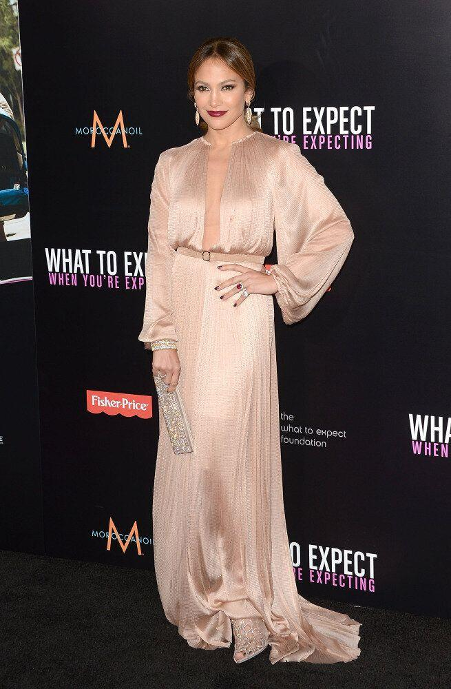 Actress Jennifer Lopez attends the Los Angeles premiere of <em>What To Expect When You're Expecting </em> wearing a cream dress with deep red lips.